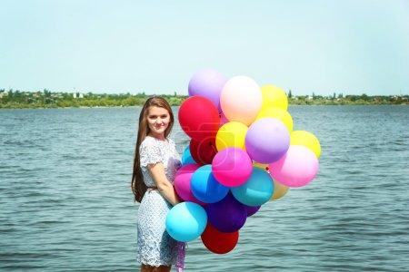 Photo pour Femme heureuse avec des ballons colorés sur la côte de la rivière - image libre de droit