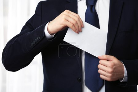 Businessman putting envelope in suit pocket
