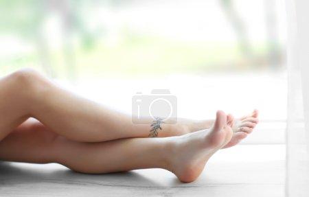 Photo pour Jambes féminines avec tatouages sur le rebord de la fenêtre - image libre de droit
