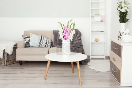 Room with bouquet of flowers in vase on wooden table