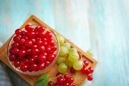 Fresh red currant and orange in glass bowl on wooden box