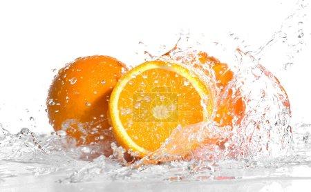 Photo pour Oranges fraîches dans les éclaboussures d'eau isolées sur blanc - image libre de droit