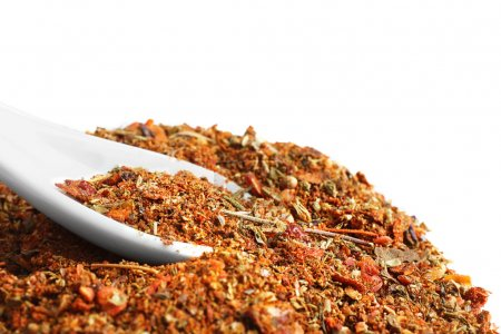Heap of mixed spices with spoon on white background