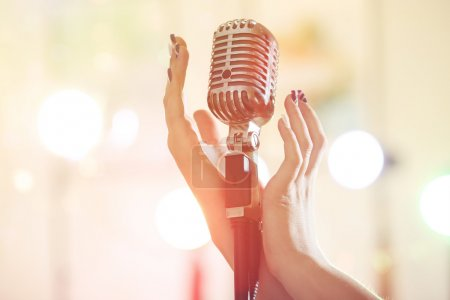Female hand with vintage microphone