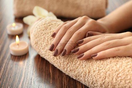 Photo pour Femelle des mains avec manucure brun sur la serviette - image libre de droit