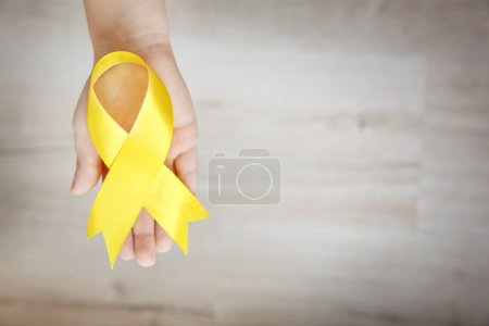 Baby hand holding yellow ribbon