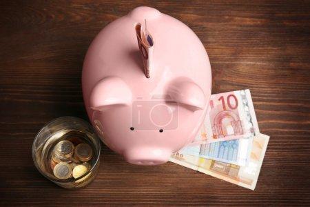 Photo pour Tirelire rose, verre d'eau et euros sur fond bois. Concept d'économie d'eau - image libre de droit