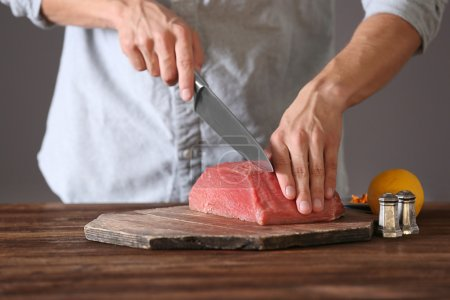 Photo for Butcher cutting pork meat on kitchen - Royalty Free Image