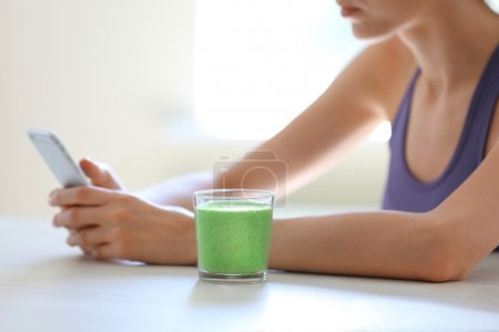 girl sitting at table with smoothie drink
