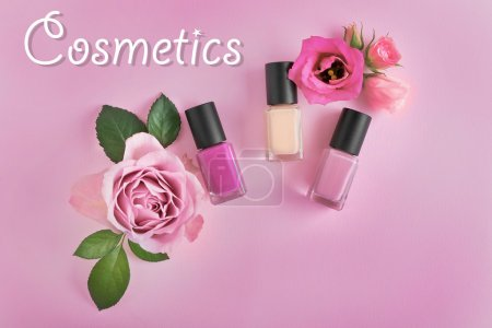 Nail polishes and flowers on pink background