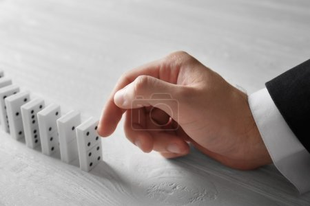 Hand pushing dominoes