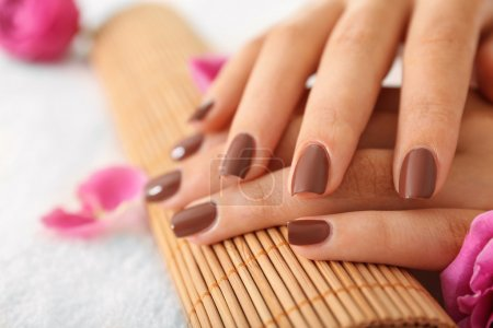Photo pour Femelle des mains avec manucure brun sur la natte de bambou osier - image libre de droit