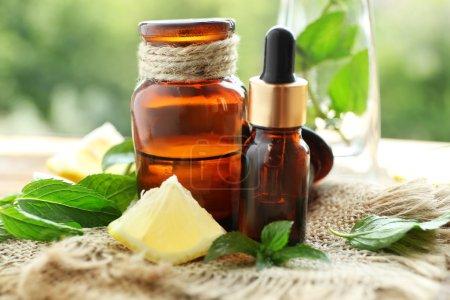 Photo pour Bouteilles d'huile de menthe, de chaux et de feuilles fraîches sur la table, flou fond naturel - image libre de droit