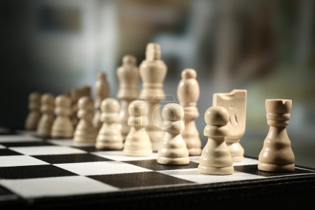 Chess board with chess pieces on dark background
