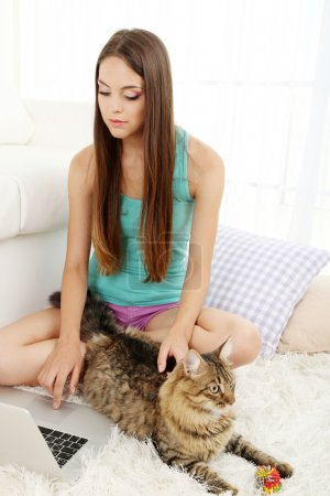 Beautiful young woman with cat sitting on carpet in room