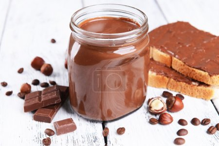 Sweet chocolate cream in jar on table close-up