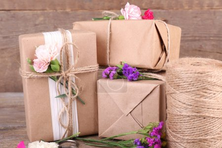 Beautiful gifts with flowers and decorative rope, on old wooden background