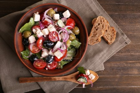 Greek salad served in brown bowl with bread on sacking napkin on wooden background