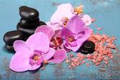 Růžové květy tropických orchidejí a wellness kameny
