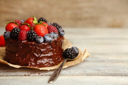 Tasty chocolate cake with different berries on woo...