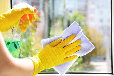 Photo pour Nettoyage des fenêtres avec chiffon spécial et nettoyant - image libre de droit