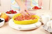 Pečení chutný koláč a ingredience pro to na stole v kuchyni