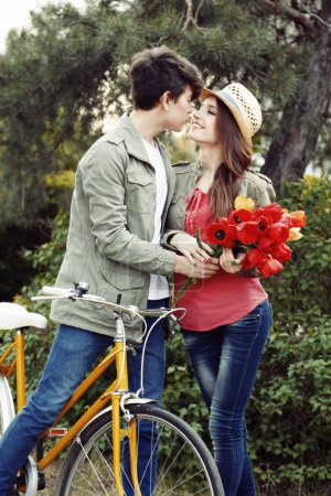 Young couple with bicycle in park