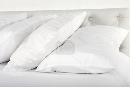Photo pour Oreillers blancs sur le lit dans la chambre - image libre de droit