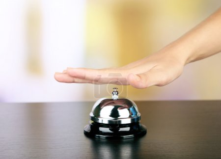 Female hand ring bell on  hotel reception desk