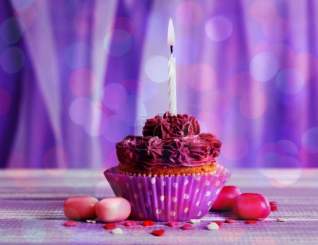 Photo for Tasty cupcake with candle on bright purple background - Royalty Free Image