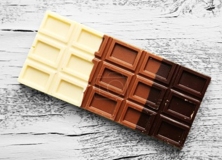 Milchschokolade auf farbigem Holzhintergrund