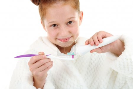 Beautiful little girl in bathrobe holding toothbrush and toothpaste isolated on white
