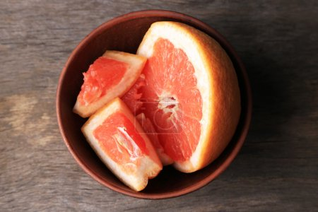 Photo for Ripe chopped grapefruit  in bowl, on wooden background - Royalty Free Image