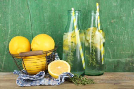 Photo for Tasty cool beverage with lemon and thyme, on wooden background - Royalty Free Image