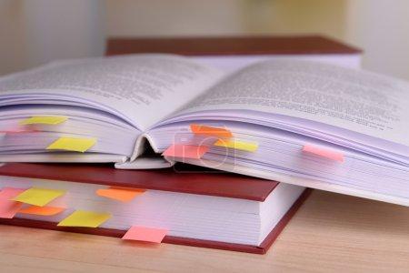 Photo pour Livres avec signets sur la table sur fond lumineux - image libre de droit