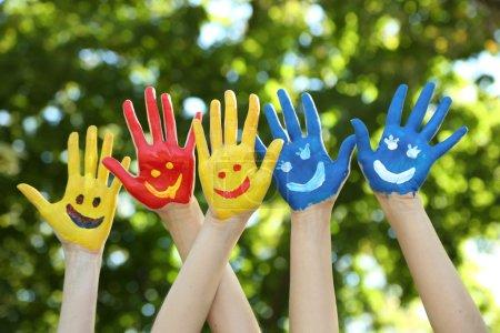 Photo pour Souriant coloré mains sur fond naturel - image libre de droit