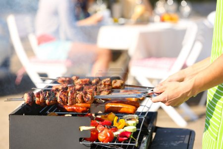 Photo for Young friends having barbecue party, outdoors - Royalty Free Image