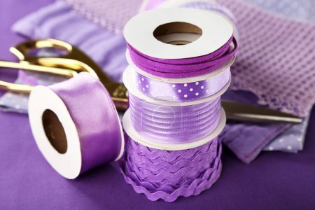 Ribbons with scissors and fabrics close up