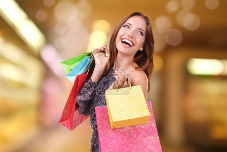 Photo for Shopping concept. Beautiful young woman with shopping bags on bright background - Royalty Free Image