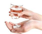 Ruce s prášky a sklenicí vody