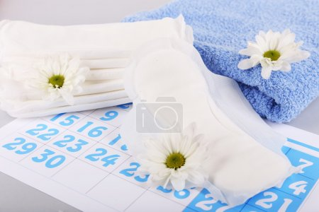 Sanitary pads, calendar, towel and white flowers