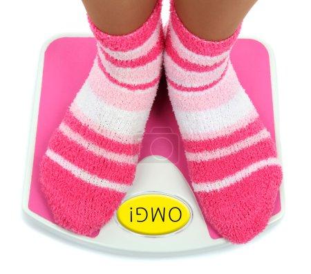 Feet in pink socks on scales