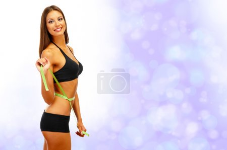 Beautiful young woman with measuring tape on bright background