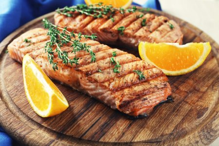 Photo for Grilled salmon  and orange slices on cutting board on wooden background - Royalty Free Image