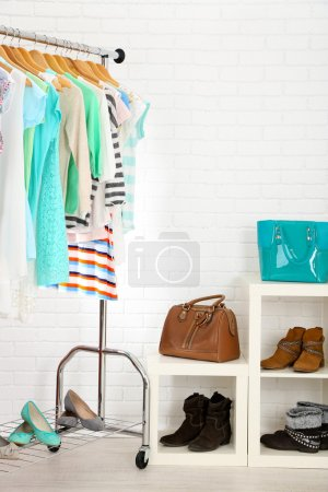 Photo for Different clothes on hangers, shoes on shelves in shop - Royalty Free Image
