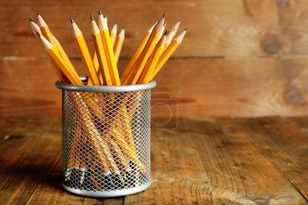 Photo pour Crayons en porte-métal sur fond bois rustique - image libre de droit
