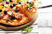 Finom pizzát szolgálnak fel, a fából készült asztal
