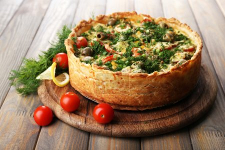 Photo for Vegetable pie with broccoli, peas, tomatoes and cheese on wooden background - Royalty Free Image