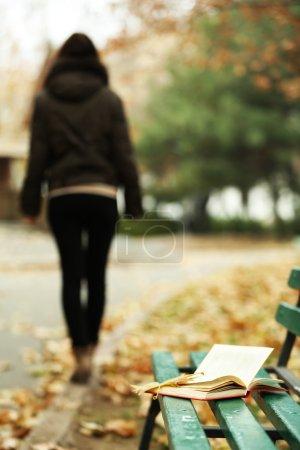 Livre a laissé sur le banc avec la silhouette de jeune fille, s'éloignant en automne parc