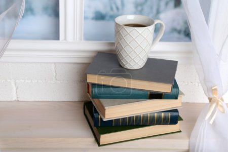 Books and cup on the windowsill